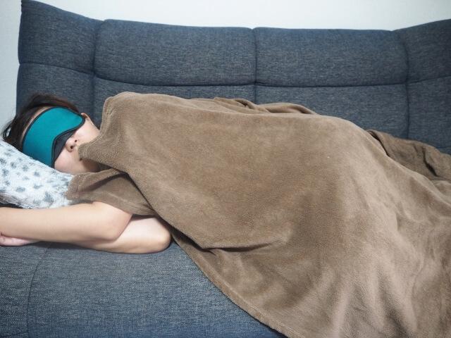 毛布を掛けて仮眠する女性