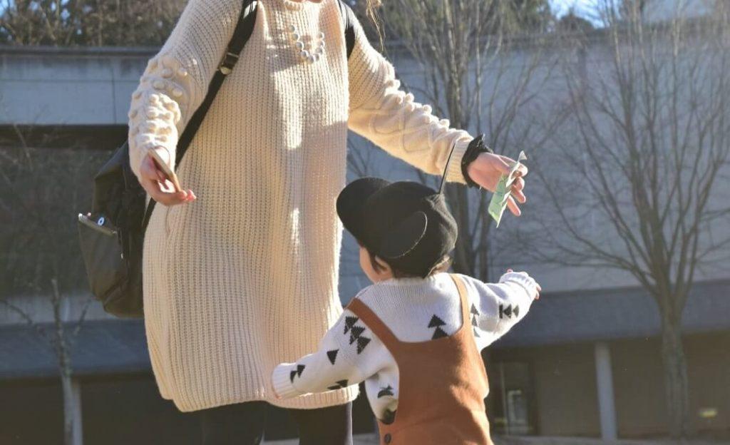 リュックを背負って子と遊ぶ母