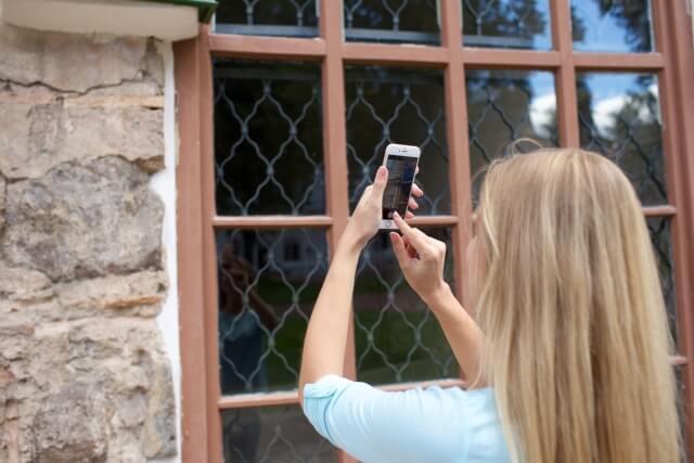 窓の写真を撮る女性