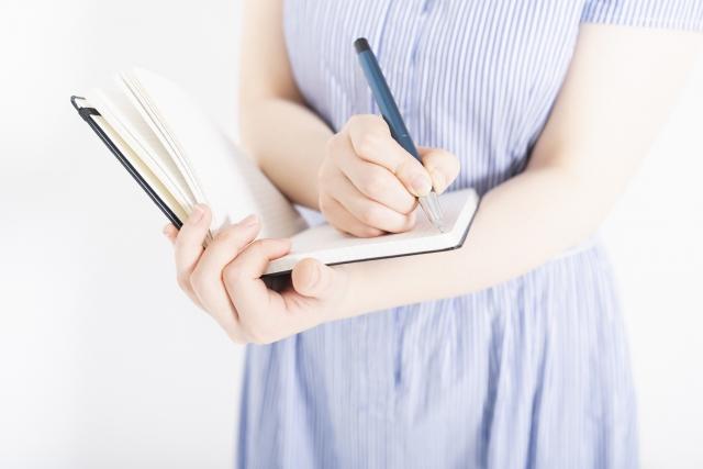 ノートにメモする女性