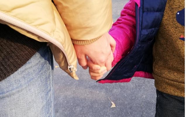 手を繋ぐ厚着の親子